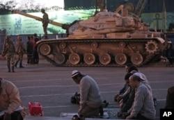 Des manifestants priant sur la place Tahrir du Caire, à proximité d'un char de l'armée