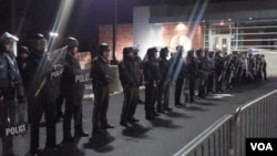 FILE - Ferguson police behind barricades before they came forward and arrested between four to six people, Nov. 19, 2014. (A. Tanzeem/VOA)