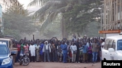 People stand near the Radisson hotel after al-Qaida launched a deadly attack on guests, in Bamako, Mali, Nov. 20, 2015.