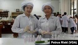 Dua mahasiswa Fakultas Farmasi Universitas Surabaya membuat cairan penyanitasi tangan untuk mencegah penyebaran virus corona di kampus, 10 Maret 2020. (Foto: Petrus Riski/VOA)