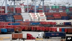 FILE - Two trucks move shipping containers at the Port of Long Beach in Long Beach, California, Feb. 17, 2015.