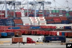 FILE - Two trucks move shipping containers at the Port of Long Beach, Feb. 17, 2015, in Long Beach, California.