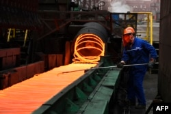 FILE - A Chinese employee sorts hot red steel at a steel plant in Zouping in China's eastern Shandong province, March 5, 2018. China has warned this month that it will retaliate if the United States damages its economic interests.