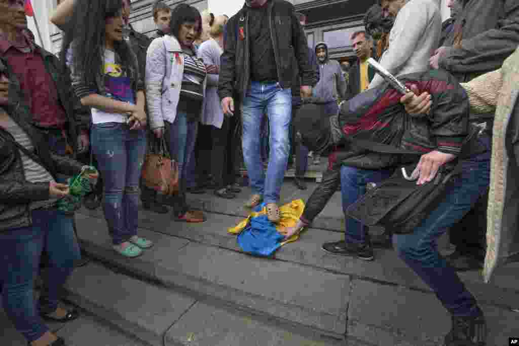 Pro-Russian activists trample a Ukraine flag as other celebrate the capture of an administration building in the center of Luhansk, Ukraine, April 29, 2014.