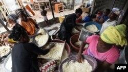 Les femmes préparent la semoule de manioc pour la préparation du plat d'accompagnement attiéké à Abidjan, le 22 mai 2018.