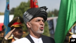 "Afghan President Ashraf Ghani sings the national anthem after putting flowers on the ""Independence Minaret"" monument during Independence Day celebrations at Defense Ministry in Kabul, Aug. 18, 2016."