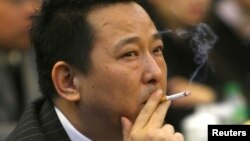 FILE - Liu Han, former chairman of Hanlong Mining, smokes a cigarette during a conference in Mianyang, Sichuan province.