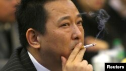 FILE - Liu Han, former chairman of Hanlong Mining, smokes during a conference in Mianyang, Sichuan province.