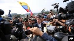 Pemimpin oposisi Venezuela yang memproklamirkan diri sebagai Presiden Sementara, Juan Guaido (tengah) memberi keterangan kepada pers dan pendukungnya di luar pangkalan udara La Carlota, Caracas, Venezuela, 30 April 2019.