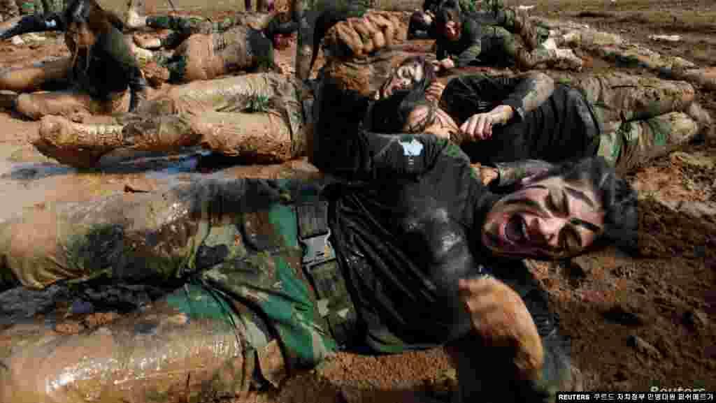 이라크 에르빌 소란의 군부대에서 쿠르드자치정부 군사 조직 페쉬메르 특공대원들이 진흙탕 위를 기어가고 있다.