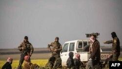 Sujetos sospechosos de ser combatientes del Estado Islámico llegan a un centro de investigación en Baghuz, Siria.