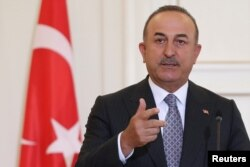 FILE - Turkish Foreign Minister Mevlut Cavusoglu speaks during a joint news conference with his Greek counterpart Nikos Dendias at the Ministry of Foreign Affairs in Athens, Greece, May 31, 2021.