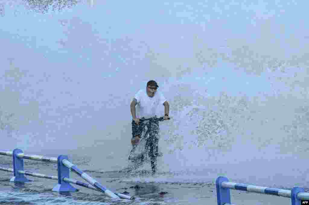 A man rides a bicycle as waves, caused by Typhoon In-Fa further down the Chinese coast, surge over a barrier along the seacoast in Qingdao in China's eastern Shandong province, July 25, 2021.