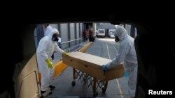 Trabajadores de una funeraria transportan el cuerpo de una persona que murió a causa del coronavirus dentro de un sarcófago de cartón, en la ciudad de México. Junio 5 de 2020.