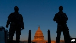 FILE - National Guard soldiers stand their posts around the Capitol at sunrise in Washington, March 8, 2021.