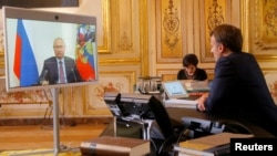 Presiden Perancis Emmanuel Macron berbicara dengan Presiden Rusia Vladimir Putin melalui panggilan video, di Istana Elysee di Paris, Perancis, 26 Juni 2020.