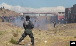 Independent miners clash with the police as they run from clouds of tear gas during protests in Panduro, Bolivia, Aug. 25, 2016.