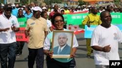 Seorang perempuan memegang foto Presiden Burundi, Pierre Nkurunziza, dalam sebuah demonstrasi di Bujumbura, Mei 2016.