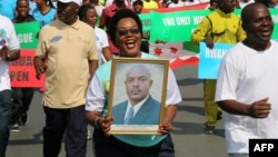 FILE - A woman holds up a picture of Burundi's President Pierre Nkurunziza during a rally in Bujumbura on May 14, 2016, commemorating the one-year anniversary of the failed attempt of a government coup. Authorities in Burundi arrested 11 students last week for defacing a photo of President Pierre Nkurunziza.