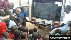 FilmAid worker with children during mobile cinema screening in Kakuma Refugee Camp, Kenya, on May 8, 2013. (Courtesy: FilmAid)