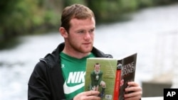 """Pemain Manchester United Wayne Rooney berpose dengan bukunya """"Wayne Rooney: My Story So Far"""", di Manchester, Inggris (10/8/2006). Karena cedera Rooney tidak turun bertanding melawan Klub Chelsea hari Minggu ini."""