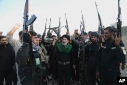 ایک عسکری شیعہ گروپ اپنے ہتھیار لہرا کر نعرے لگا رہا ہے۔ فائل فوٹو