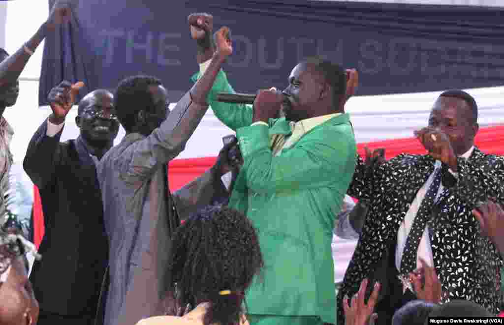 Peter Garang is joined on stage by fans at the Abyei fundraiser at Freedom Hall, Juba, October 2013.
