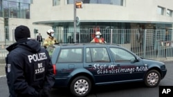 """Sebuah mobil berhenti di depan kantor kanselir Jerman Angela Merkel di Berlin, Jerman, setelah menabrak gerbang depan gedung tersebut, Rabu, 25 November 2020. Di badan mobil tersebut terdapat tulisan slogan """"hentikan kebijakan-kebijakan global"""".(Foto AP / Michael Sohn)"""