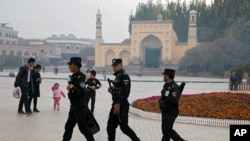 FILE - Uyghur security workers walk near the Id Kah Mosque in Kashgar in western China's Xinjiang region, Nov. 4, 2017.
