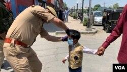 سری نگر میں ایک بچے کو ماسک پہنایا جا رہا ہے (فائل)