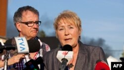 Quebec Premier Pauline Marois (foreground) speaks to reporters in Lac Megantic in this July 6, 2013, file photo.