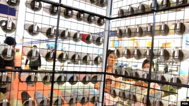 Exhibitors examine their company's yarn display at Saigon Tex, a garment and textile expo.