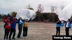 22일 한국의 탈북자단체들이 경찰의 저지로 임진각에서 대북 전단을 날리는데 실패하자, 강화도로 옮겨 전단을 매단 풍선을 날리고 있다.