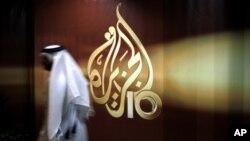 FILE - A Qatari employee of Al Jazeera Arabic language TV news channel walks past the network's logo, in Doha, Qatar, Nov. 1, 2006.