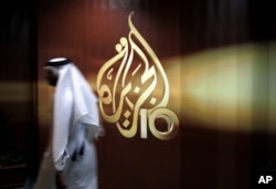 FILE - A Qatari employee of the Al Jazeera Arabic-language TV news channel walks past the logo of Al Jazeera in Doha, Qatar.