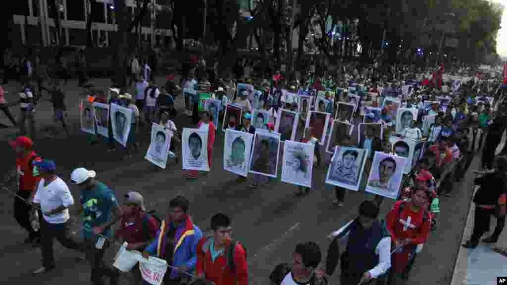 Relatives holding posters with images of the missing students march in protest for the disappearance of 43 students in the state of Guerrero, in Mexico City, Nov. 5, 2014.