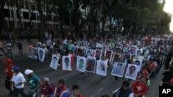 Para kerabat memegang poster bergambar 43 mahasiswa yang hilang dalam protes di Mexico City (5/11). (AP/Marco Ugarte)