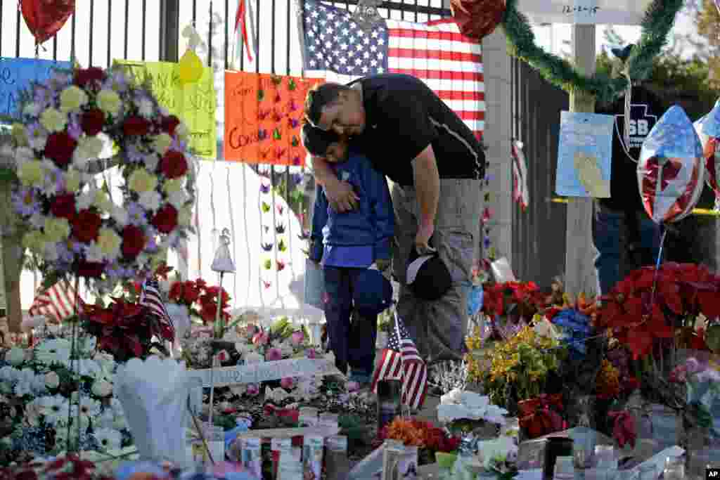Gary Mendoza, and his son Michael pay their respects at a makeshift memorial site honoring shooting victims in San Bernardino, California. Thousands of employees of San Bernardino County are preparing to return to work, five days after a county restaurant inspector and his wife opened fire on a gathering of his co-workers, killing 14 people and wounding 21.