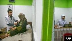 Dr. Gamal Albinsaid (kiri) memeriksa pasien di Klinik Bumi Ayu di Malang, Jawa Timur. (AFP)