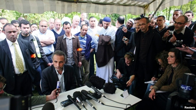 FILE - Tariq Ramadan talks to the media after a conference at the Er-Rahma mosque in Nantes, western France, Apr. 25, 2010.