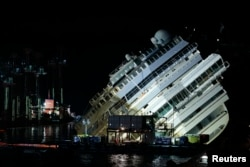 """The capsized cruise liner Costa Concordia lies on its side during the """"parbuckling"""" operation next to Giglio Island. Sept. 16, 2013."""