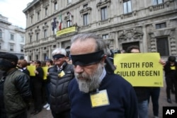 FILE - Amnesty International activists stage a flash mob asking for truth about the death of Italian student Guido Regeni, outside Milan's city hall, Italy, April 24, 2016.