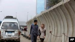 2014年11月27日星期四,一對夫婦步行通過埃及外交部週圍的混凝土障礙物。