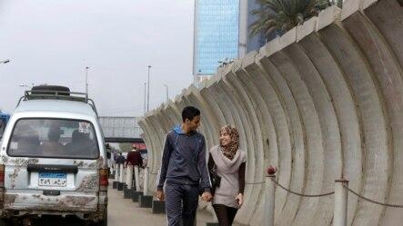 2014年11月27日星期四,一对夫妇步行通过埃及外交部周围的混凝土障碍物。