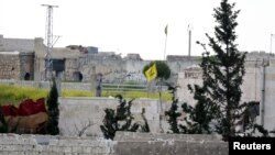 FILE - A Hezbollah flag flutters in a government-controlled area, as seen from the rebel-controlled area of Karm al-Tarab frontline, near Aleppo international airport, April 22, 2015.