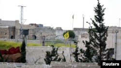 FILE - A Hezbollah flag flutters in a government-controlled area, as seen from the rebel-controlled area of Karm al-Tarab, near Aleppo's airport, April 22, 2015.