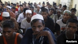 Sekelompok migran Rohingya dan Bangladesh duduk di tempat penampungan di Lhoksukon, NAD, Indonesia, 13 Mei 2015, setelah diselamatkan kapal-kapal nelayan Aceh karena kapal mereka nyaris tenggelam. (Roni Bintang/REUTERS)