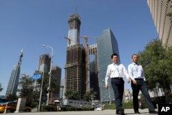 지난달 19일 중국 베이징 비지니스 중심가에서 회사원들이 공사현장 앞을 지나고 있다.