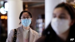 Travelers at Seattle-Tacoma International Airport wear masks Tuesday, March 3, 2020, in SeaTac, Wash. Six of the 18 Western Washington residents with the coronavirus have died as health officials rush to test more suspected cases and communities…