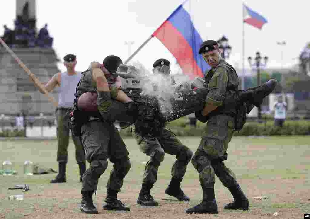 A Russian Marine uses a hammer to break a brick on top of his comrade's stomach during a Capability Demonstration at Manila's Rizal Park, the Philippines.